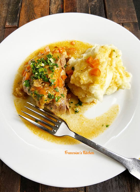 Osso Buco served with gremolata and mashed potatoes in a white plate
