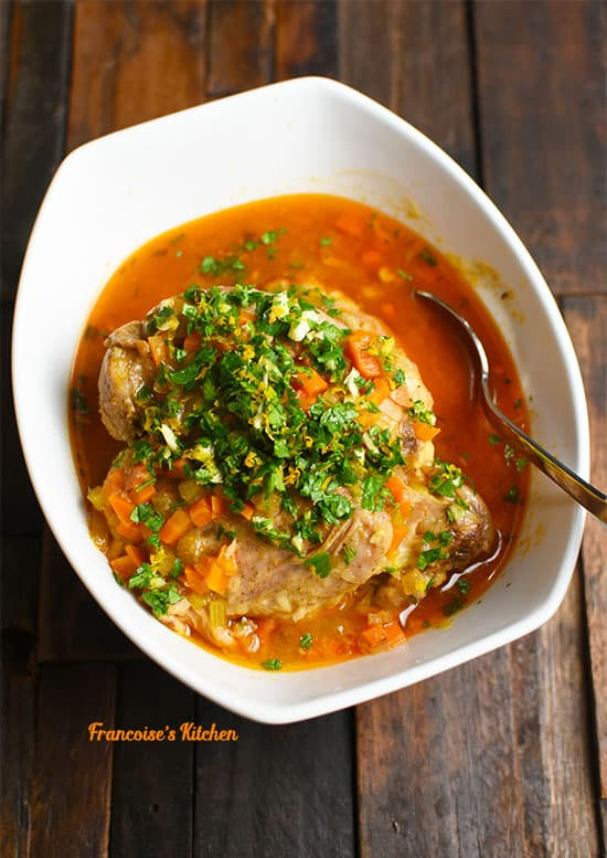 Turkey Osso Buco served in a white bowl with gremolata