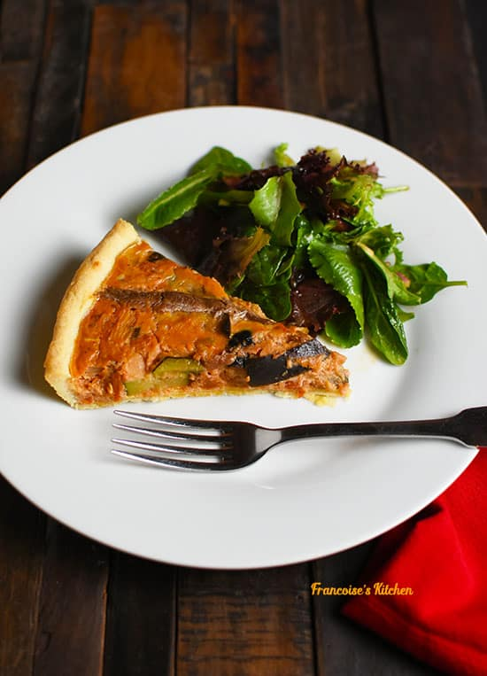 Ratatouille Anchovy Tart slice served in a plate with a green salad.