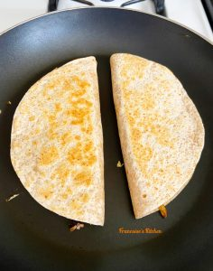 Chicken black bean quesadilla cooked in a skillet on the stove