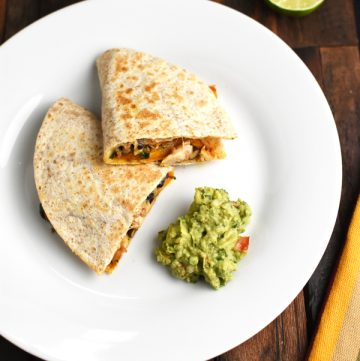 Chicken Black Bean Quesadilla served on a plate with some fresh guamole