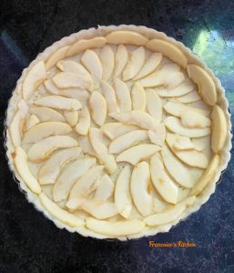 Apple slices placed on the bottom of the tart
